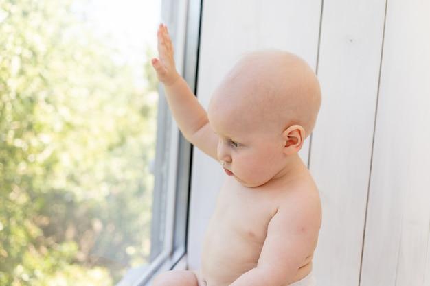 Babyjongen zittend op de vensterbank