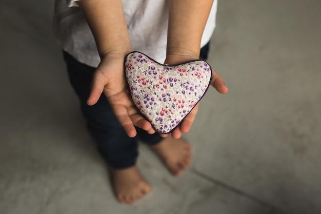 Babyjongenhanden die stuk speelgoed hart geven.