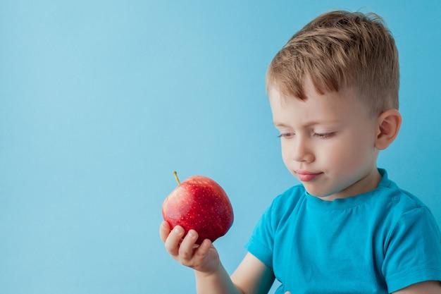 Babykind die en rode appel op blauwe achtergrond, voedsel, dieet en gezond het eten concept houden eten