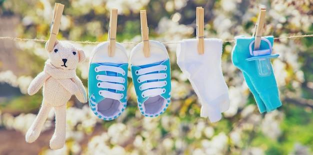Babykleding en accessoires wegen na het wassen in de open lucht op het touw.