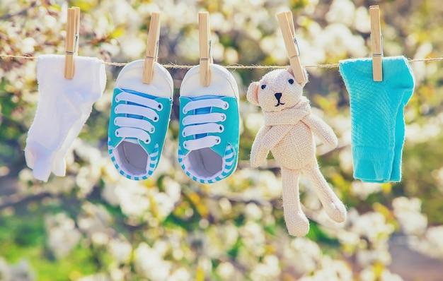 Babykleding en accessoires wegen op het touw na het wassen in de open lucht. selectieve aandacht.