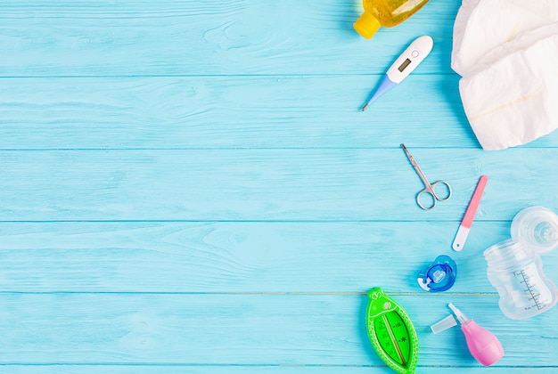 Babykleding en ander spul voor kind op blauwe achtergrond. pasgeboren baby concept. bovenaanzicht