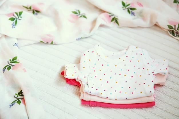 Babykleding en benodigdheden op een lichte stofachtergrond zachte, zachte en gezellige sfeer