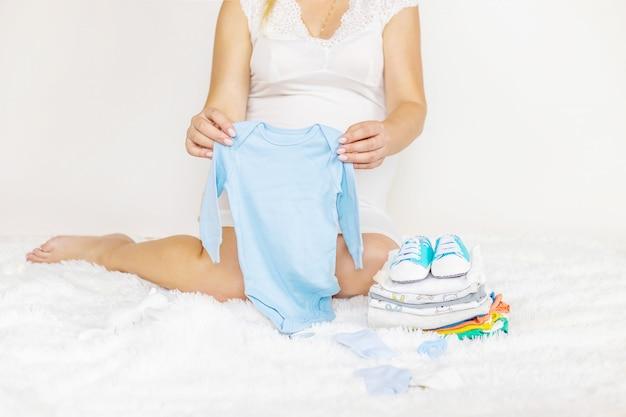 Babykleding en een zwangere vrouw.