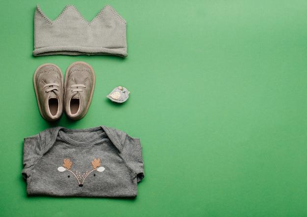 Babykleding en schoenen op groene achtergrond met lege ruimte voor tekst. bovenaanzicht, plat gelegd.