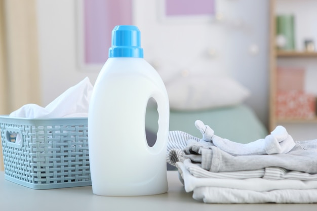 Babykleding en wasmiddelen op tafel babykleding zorgconcept