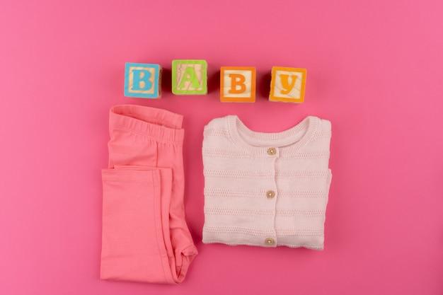 Babykleding op roze achtergrond bovenaanzicht