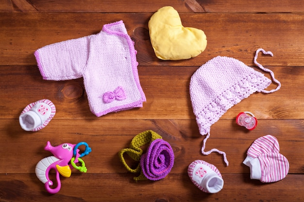 Babykleding set concept, roze gebreide kleding, speelgoed en accessoires op bruine houten achtergrond, kind pasgeboren mode doek voor meisje, moderne baby douchegift, baby kledingwinkel, bovenaanzicht plat lag