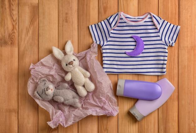 Babykleding, speelgoed en cosmetica op houten tafel, plat gelegd