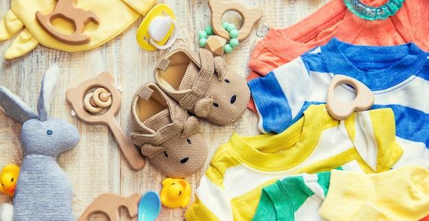 Babykleertjes en accessoires op een lichte achtergrond