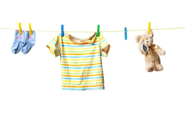 Babykleertjes en een teddybeer drogen aan een touw geïsoleerd op een witte achtergrond