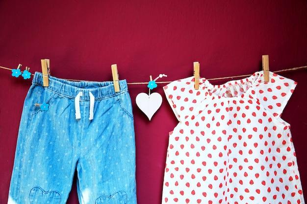 Babykleertjes en goederen die aan wasknijpers aan de waslijn hangen op een gestructureerde muurachtergrond