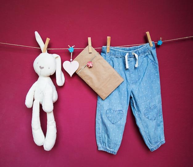 Babykleertjes en speelgoed hangen aan wasknijpers aan de waslijn op een gestructureerde muurachtergrond