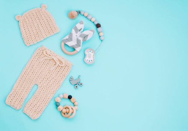 Babykleertjes, fopspeen en houten speelgoed op lichtblauw
