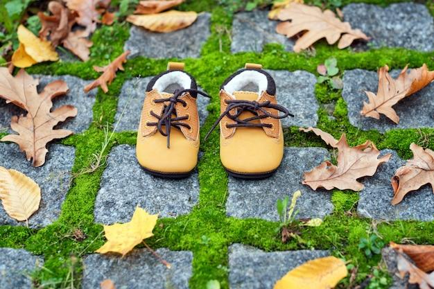 Babylaarzen in de herfstpark. kinderschoenen met gele bladeren buitenshuis.