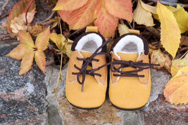 Babylaarzen in het bos. kid schoenen met herfstbladeren buitenshuis.