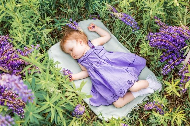 Babymeisje 1 jaar oud slapen in de natuur tussen de bloemen