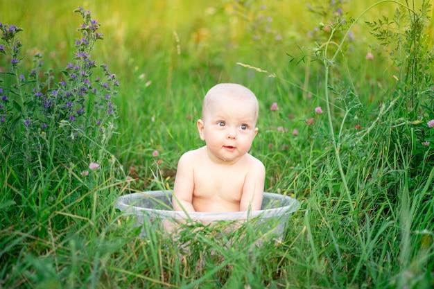 Babymeisje 10 maanden oud baadt in een bassin in het gras in de zomer.