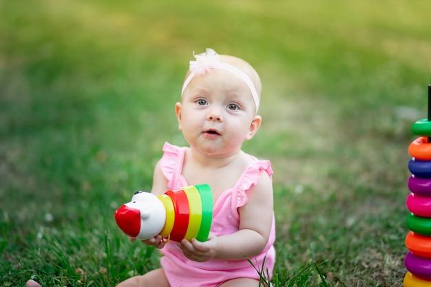 Babymeisje 10 maanden oud zittend op het gras in de zomer en piramide spelen, vroege ontwikkeling van kinderen, buitenspellen