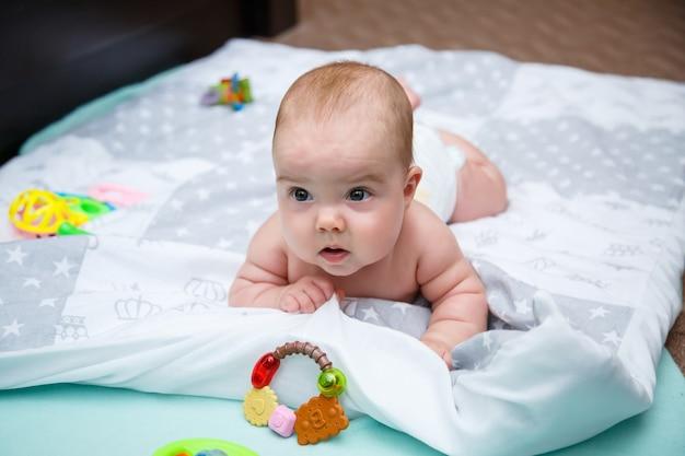 Babymeisje 3 maanden oud ligt op het bed. baby zonder kleren in een luier