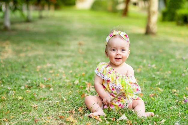 Babymeisje 7 maanden oud zittend op een groen gazon in een gele jurk en spelen met een stuk speelgoed, wandelen in de frisse lucht, ruimte voor tekst