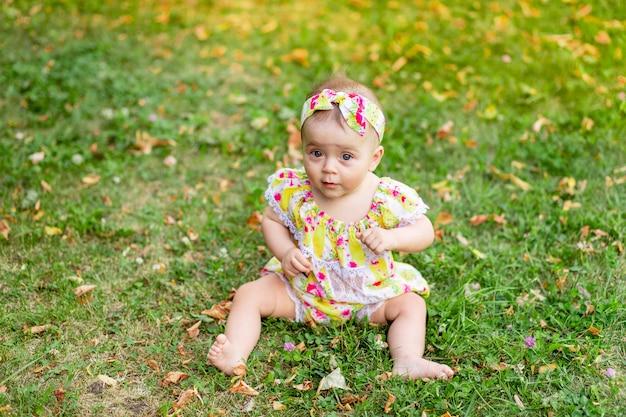 Babymeisje 7 maanden oud zittend op het groene gras in een gele jurk, wandelen in de frisse lucht
