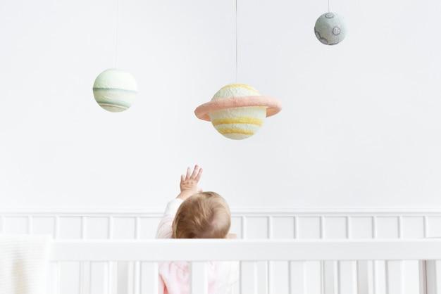 Babymeisje dat naar het universum reikt