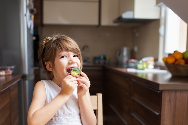 Babymeisje die een snack hebben thuis