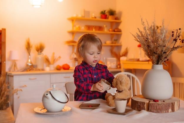 Babymeisje die hebbend ontbijt in de keuken met een teddybeer glimlachen