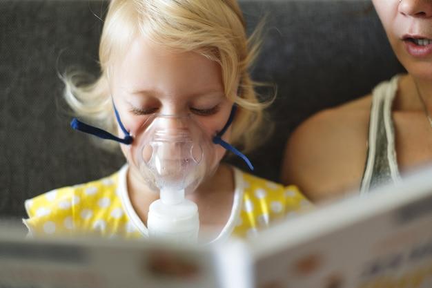 Babymeisje die inhaleert met masker op haar gezicht