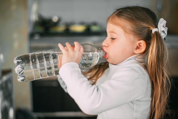 Babymeisje drinkt gretig water uit een plastic fles met een inhoud van een liter erg zoet