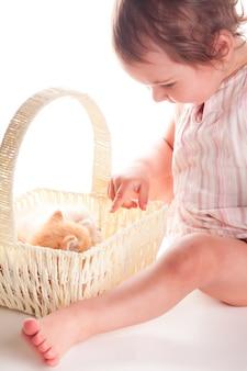 Babymeisje en katje dat op witte achtergrond wordt geïsoleerd