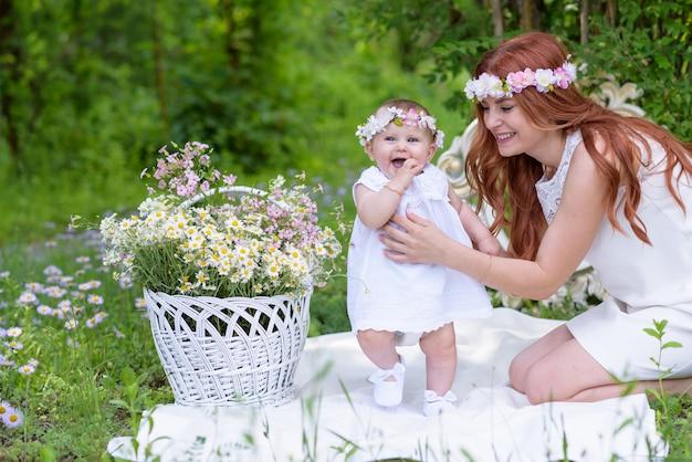 Babymeisje en moeder in witte kleding in een de lentetuin met bloemkroon