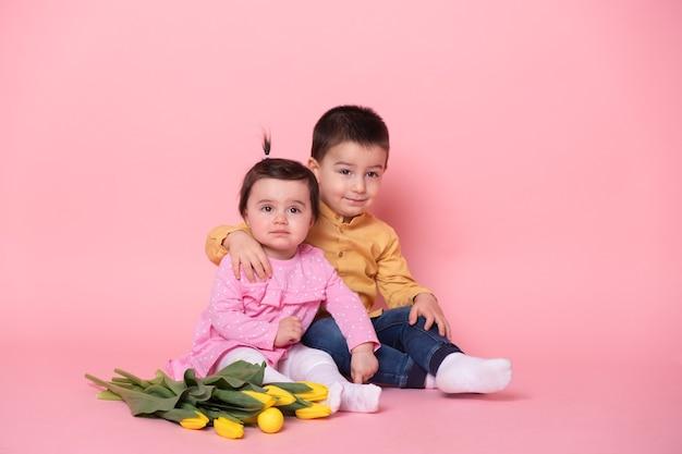 Babymeisje en oudere broer jongen op roze studio