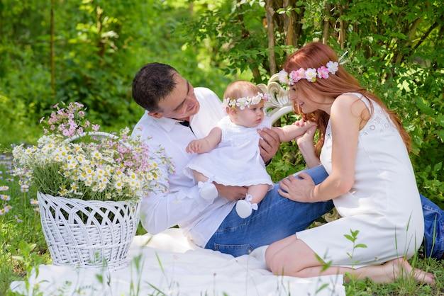 Babymeisje en ouders in witte kleding in een de lentetuin met bloemkroon