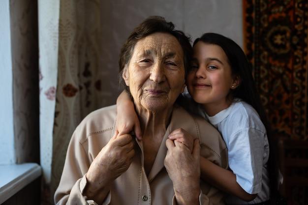 Babymeisje en zeer oude vrouw. klein kind knuffelen grootmoeder. kleindochter