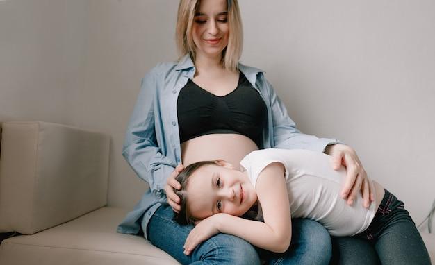 Babymeisje en zwangere moeder liefdevolle zusje naast moeders buik. gelukkig gezin