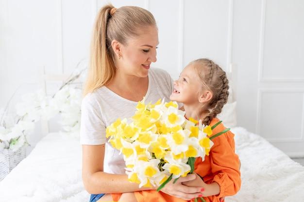 Babymeisje geeft bloemen aan haar moeder voor een vakantie op het bed thuis, het concept van liefde en moederschap of moederdag