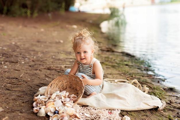 Babymeisje gekleed als een zeeman op een zandstrand met schelpen aan zee