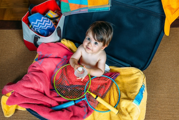 Babymeisje glimlachend zittend in een koffer klaar om op vakantie te gaan