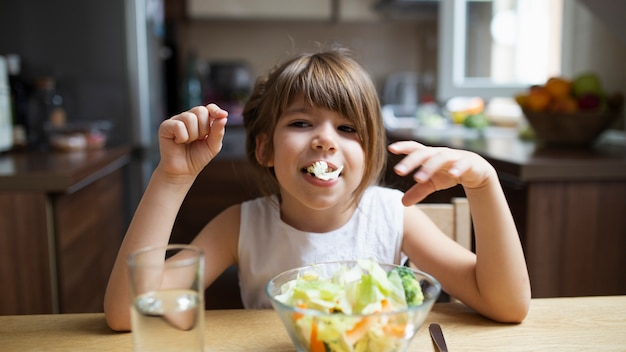 Babymeisje het spelen met salade terwijl het eten