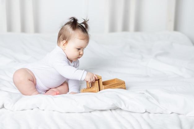 Babymeisje houten speelgoed typemachine spelen op het bed thuis, het concept van spelen en ontwikkeling van kinderen