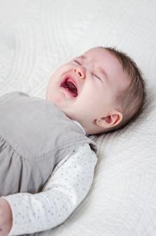 Babymeisje huilend over wit bedovertrek