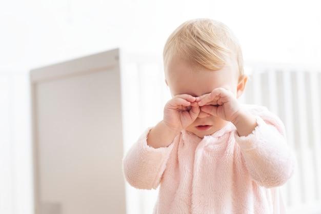Babymeisje huilt en wrijft in haar ogen