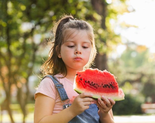 Babymeisje in aard die een watermeloenplak hebben