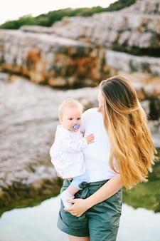 Babymeisje in de armen van haar moeder op een rotsachtig strand