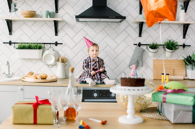 Babymeisje in de keuken. de eerste verjaardag van de baby. mooi meisje viert verjaardagsfeestje met ballonnen en verjaardagstaart. een jaar feest. schattige baby meisje in roze verjaardag hoed.