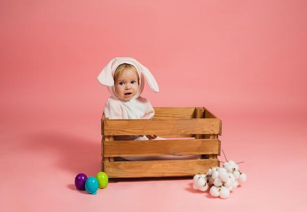 Babymeisje in een konijnenkostuum zit in een houten kist met kleurrijke eieren op een roze muur