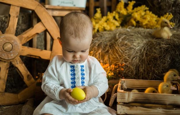 Babymeisje in een linnen jurk zit op een rietje en houdt een paasei. pasen voor kinderen