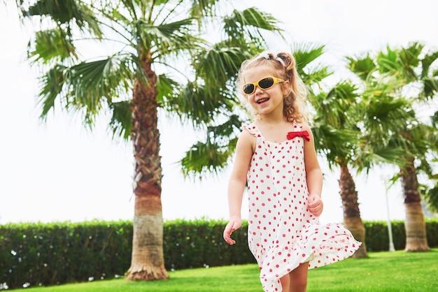 Babymeisje in een park in de buurt van bomen.